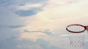 Обручи и сети баскетбола тряся шарик упали небо предпосылки с облаками и солнцем летом сток-видео