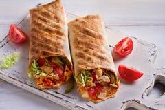 Обручи цыпленка с томатами, соленьями, капустой и луком на белых прерывая доске и деревянном столе стоковые фото