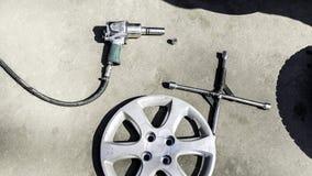 Обслуживание автомобиля, гайка приспособления колеса автомобиля на белой предпосылке, стоковое изображение