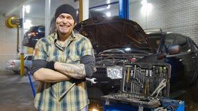 обслуживание замены масла автомобиля шара поднятое подъемом Зверский человек механика готовя автомобиль и оскалы стоковые изображения rf