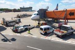 Обслуживание пассажирского самолета в авиапорте перед полетом, земной деятельностью на авиапорте Берлина стоковое изображение rf