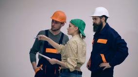 Обсуждать эскиз нового здания Люди на концепции работы Женские контролер и архитекторы обсуждают о конструкции сток-видео