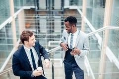 Обсуждение 2 multiracial бизнесменов в современной зале Стоковая Фотография RF