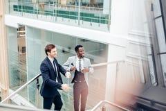 Обсуждение 2 multiracial бизнесменов в современной зале Стоковое Изображение