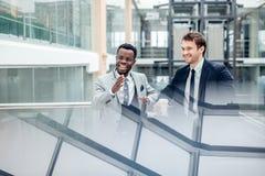 Обсуждение 2 multiracial бизнесменов в современной зале Стоковые Фото