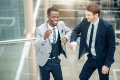 Обсуждение 2 multiracial бизнесменов в современной зале Стоковое Изображение RF