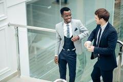 Обсуждение 2 multiracial бизнесменов в современной зале Стоковое Фото