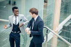 Обсуждение 2 multiracial бизнесменов в современной зале Стоковые Изображения RF