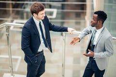 Обсуждение 2 multiracial бизнесменов в современной зале Стоковые Фотографии RF
