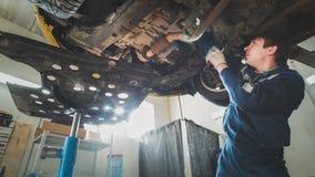 Обслуживание автомобиля автомобиля - механик работника проверяет дно автомобиля Стоковые Изображения RF