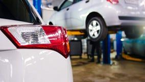 Обслуживание автомобиля - красные backlights белого автомобиля в противоположности подняли автомобиль Стоковая Фотография RF