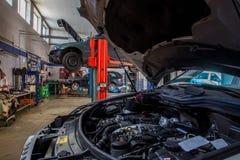 обслуживание замены масла автомобиля шара поднятое подъемом стоковые фото