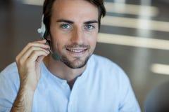 Обслуживание клиента говоря на шлемофоне в офисе Стоковое Изображение