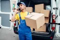 Обслуживание поставки груза, курьер с коробкой и телефон Стоковое Изображение