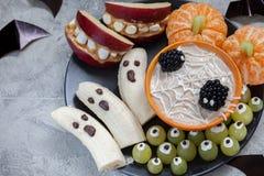 Обслуживания хеллоуина плодоовощ Призраки банана и тыквы Клементина оранжевые, держатели изверга Яблока и сеть паука Стоковое Изображение RF