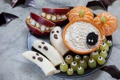 Обслуживания хеллоуина плодоовощ Призраки банана и тыквы Клементина оранжевые, держатели изверга Яблока и сеть паука Стоковое фото RF
