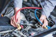 Обслуживать кондиционера автомобиля промежуточные трубы механика для refill freon стоковые фотографии rf