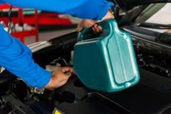 Обслуживая механик лить новую смазку масла в двигатель автомобиля стоковое изображение