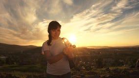 Обтекатель втулки извива молодой женщины стоя на заходе солнца на вечере лета сток-видео