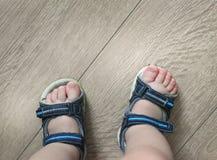 Обутые ноги младенца Сандалии ` s детей на их ногах Ботинки малыша Туристские сандалии для самых малых путешественников Новое при Стоковое Изображение RF