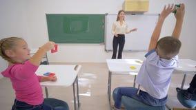Обучение детей, веселая женщина воспитателя около доски проводит когнитивный урок для милых зрачков на столе в классе  акции видеоматериалы