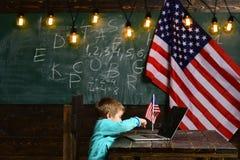 Обучение по Интернетуу или онлайн курсы дома обучая Мальчик с компьтер-книжкой для дела на американском флаге Патриотизм и стоковое фото
