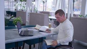 Обучение по Интернету неработающего, больного мужчины студента на кресло-каталке использует современную компьютерную технологию д видеоматериал