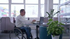 Обучение по Интернету, старшие мужские инвалиды в стеклах кресло-коляскы нося читает книгу и использует ноутбук сидя на таблице в видеоматериал