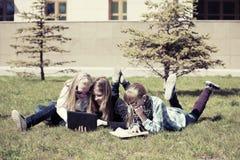 Обучите девушек лежа на траве в кампусе Стоковые Фото