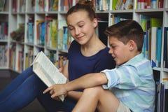 Обучите книги чтения детей в библиотеке на школе Стоковое Фото