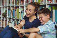 Обучите книги чтения детей в библиотеке на школе Стоковые Изображения