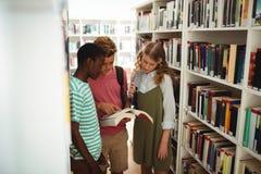Обучите книги чтения детей в библиотеке на школе Стоковые Фото