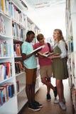 Обучите книги чтения детей в библиотеке на школе Стоковая Фотография
