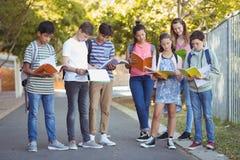 Обучите книги чтения детей на дороге в кампусе Стоковая Фотография RF
