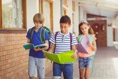 Обучите книги чтения детей пока идущ в коридоре Стоковое фото RF