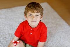 Обучите ребенк играя с Tri обтекателем втулки руки непоседы внутри помещения Стоковая Фотография