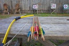 Обхватывайте для снимать и стрелок на таблице для тренировки в стрельбе на фоне цели Стоковое Фото