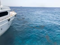 обхватывайте, сторона белого корабля и взгляд лужиц, нефтяных пятен, пакостных жидкостей, голубого моря соли, океана в tropi Стоковое Изображение