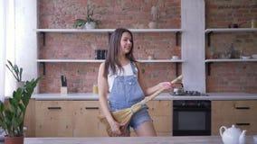 Общая чистка, сумасшедшая женщина домохозяйки с играми веника как гитара во время рутинных работ по дому видеоматериал