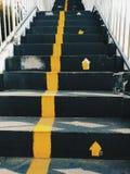 Общественная лестница с желтыми линиями для того чтобы разделить путь поднимающий вверх и путь вниз/знаки пути к поднимающим ввер Стоковые Фотографии RF
