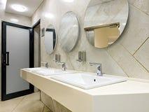 Общественная уборная с faucets и зеркалами раковин стоковое фото