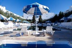 Общественный бассейн с кроватями солнца и голубыми зонтиками Стоковое фото RF