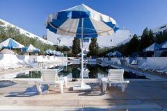 Общественный бассейн с кроватями солнца и голубыми зонтиками Стоковая Фотография RF