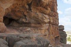 Общий вид, пещеры Badami, Karnataka Незаконченная пещера на левой стороне, и туристы входя в в пещеру 2 внизу стоковые фото
