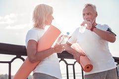 Общительная постаретая питьевая вода человека и слушать к женщине стоковая фотография rf