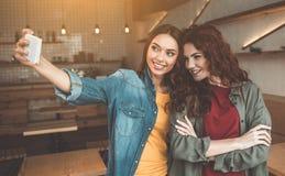 Общительные 2 девушки принимая фото на камере телефона Стоковые Фото
