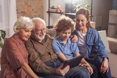 Общительные родственники наблюдая на цифровом приборе Стоковое фото RF