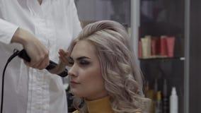 Общительный парикмахер молодой женщины делает красивые скручиваемости акции видеоматериалы