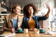 Общительные девушки принимая selfie в кафе Стоковые Изображения