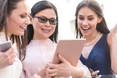 Общительные женщины смотря электронную таблетку Стоковые Изображения RF